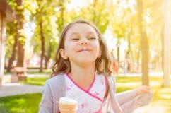 Pequeño bebé que juega la naturaleza y que come el helado fotos de archivo