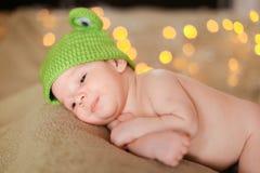 Pequeño bebé que lleva el casquillo verde y que miente en fondo de los resplandores foto de archivo