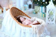 Pequeño bebé que miente en cuna en estudio del blanco de la Navidad Foto de archivo libre de regalías