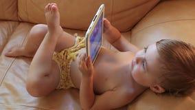 Pequeño bebé que miente en el sofá que juega con la tableta HD lleno 1920x1080 almacen de metraje de vídeo