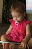 Pequeño bebé que miente en el sofá y que juega con la tableta Imagenes de archivo