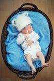 Pequeño bebé que miente en una cesta. Foto de archivo