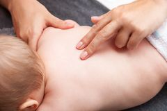 Pequeño bebé que recibe el tratamiento de la quiropráctica de ella detrás Fotos de archivo libres de regalías