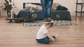 Pequeño bebé que se arrastra en el piso en el cuarto con la madre joven almacen de metraje de vídeo