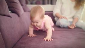 Pequeño bebé que se arrastra en el sofá casero Niño lindo que camina en todos los fours metrajes