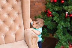 Pequeño bebé que se coloca cerca del árbol de navidad Niño año que espera el Año Nuevo 2017, concepto de familia feliz Foto de archivo libre de regalías