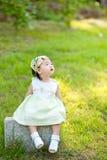 Pequeño bebé que se sienta en el césped que mira la piedra del cielo Foto de archivo libre de regalías
