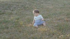 Pequeño bebé que se sienta en hierba en parque Retrato hermoso del bebé en naturaleza metrajes