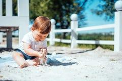 Pequeño bebé que se sienta en la arena Foto de archivo libre de regalías