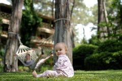 Pequeño bebé que se sienta en la hierba Imagen de archivo