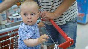 Pequeño bebé que se sienta en un carro del ultramarinos en un supermercado, mientras que su padre paga compras en el pago y envío