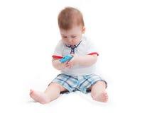 Pequeño bebé que sienta y que sostiene smartphone imágenes de archivo libres de regalías