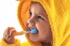 Pequeño bebé que sonríe debajo de una toalla amarilla y que cepilla sus dientes foto de archivo libre de regalías