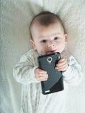 Pequeño bebé que sostiene smartphone en cama Fotografía de archivo