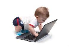 Pequeño bebé que usa la computadora portátil Imagenes de archivo