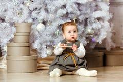 Pequeño bebé rechoncho en un vestido gris que se sienta en el nex del piso Fotografía de archivo libre de regalías