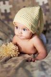 Pequeño bebé recién nacido con los ojos grandes sombrero-que hace punto en un fondo llano Imagenes de archivo
