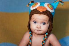 Pequeño bebé recién nacido con los ojos grandes sombrero-que hace punto en un fondo llano Fotografía de archivo libre de regalías
