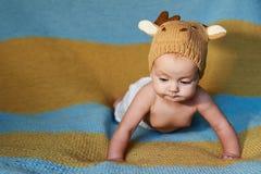Pequeño bebé recién nacido con los ojos grandes sombrero-que hace punto en un fondo llano Fotos de archivo