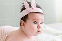 Pequeño bebé recién nacido dulce lindo que mira con la lado-cara de la curiosidad Imagen de archivo libre de regalías