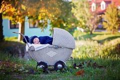 Pequeño bebé recién nacido, durmiendo en cochecito retro viejo en delanteras Fotos de archivo libres de regalías