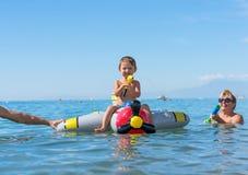 Pequeño bebé sonriente que juega con la abuela y el abuelo en el mar en el avión de aire Emociones humanas positivas, sensaciones Fotos de archivo libres de regalías