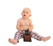 Pequeño bebé sorprendido con los pantalones de tela escocesa de la amoladora de café que llevan Fotos de archivo libres de regalías