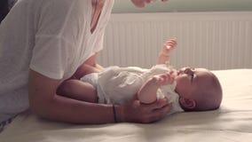 Pequeño bebé y su madre que caminan afuera durante puesta del sol La madre es que detiene y de cosquilleo de su bebé, babywearing metrajes