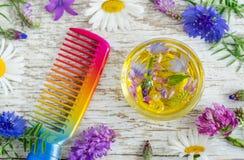 Pequeño bol de vidrio con aceite cosmético del aroma con los extractos de las flores y el peine del pelo Ingredientes del cosméti fotografía de archivo