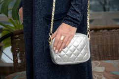 Pequeño bolso de cuero de plata acolchado elegante en las manos de una molestia Imagenes de archivo