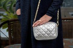 Pequeño bolso de cuero de plata acolchado elegante en las manos de una molestia Imágenes de archivo libres de regalías