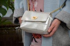 Pequeño bolso de cuero de plata elegante en las manos de un fashionista Imagenes de archivo
