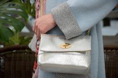 Pequeño bolso de cuero de plata elegante en las manos de un fashionista Imagen de archivo