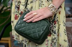 Pequeño bolso de cuero verde acolchado elegante en las manos de un fashi Imagen de archivo libre de regalías
