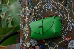 Pequeño bolso de cuero verde elegante en las manos de un fashionista Foto de archivo