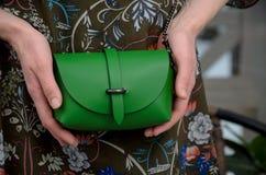 Pequeño bolso de cuero verde elegante en las manos de un fashionista Foto de archivo libre de regalías