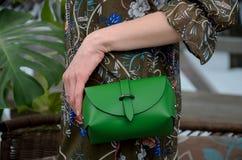 Pequeño bolso de cuero verde elegante en las manos de un fashionista Fotografía de archivo