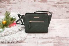 Pequeño bolso femenino verde en un fondo de madera, rama del abeto con las decoraciones Concepto de la moda con el espacio para e Imagenes de archivo