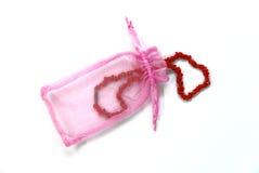 Pequeño bolso rosado con el collar rojo Fotografía de archivo libre de regalías