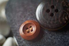 Pequeño botón de madera de la ropa al lado de un botón grande de la ropa encendido fotografía de archivo