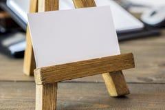Pequeño caballete de madera con el papel Imagenes de archivo
