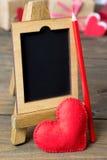 Pequeño caballete de madera, corazón rojo hecho del fieltro Fotografía de archivo