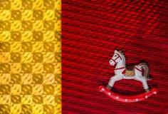 Pequeño caballo mecedora de la Feliz Año Nuevo sobre los fondos texturizados brillantes de colores rojos y amarillos Foto de archivo