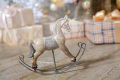 pequeño caballo mecedora de madera debajo del árbol de navidad con los regalos Foto de archivo libre de regalías