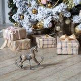 pequeño caballo mecedora de madera debajo del árbol de navidad con los regalos Fotos de archivo libres de regalías