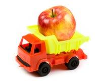 Pequeño camión con una manzana roja grande Imagenes de archivo