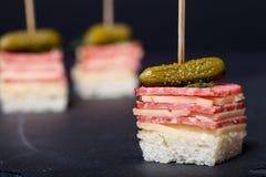 Pequeño canape de los bocados con el salami, el queso y la salmuera en el pincho encendido Fotografía de archivo
