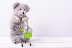 Pequeño carro de la compra y un oso de peluche Imagen conceptual para la venta de las fantasías de los juguetes o de los niños Foto de archivo libre de regalías