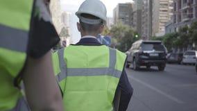 Pequeño casco del equipo y del constructor de seguridad del trabajador o del inspector del camino que lleva que camina con el ayu almacen de metraje de vídeo