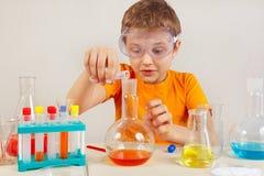 Pequeño científico elegante en las gafas de seguridad que hacen experimentos químicos en laboratorio fotografía de archivo libre de regalías